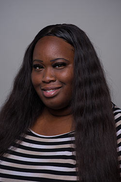 Kayla Jones posing for a headshot photo with a gray background