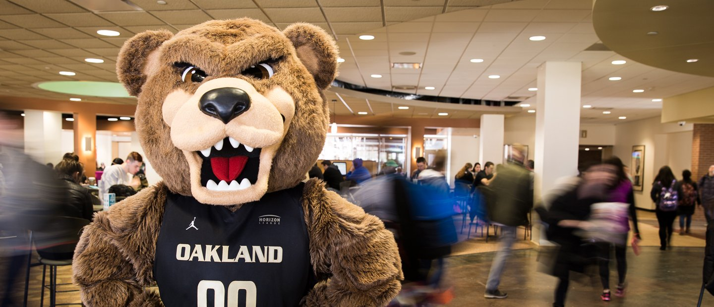 The Grizz bear wearing a jersey that says Oakland on it, with people walking through the room behind him