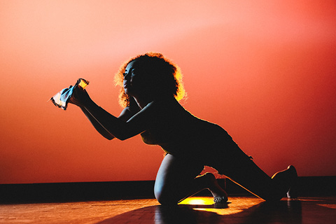 female performer on her knees on a stage with red lighting