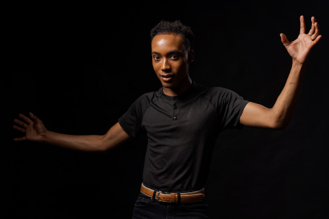 young man in a black shirt standing with his arms spread wide