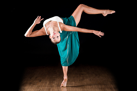 female dancer leaning backwards with face towards camera and one leg raised in the air