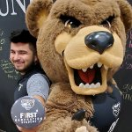 Ernesto Duran-Gutierrez, holding a First Generation Oakland University button, posing with the Grizz bear mascot..