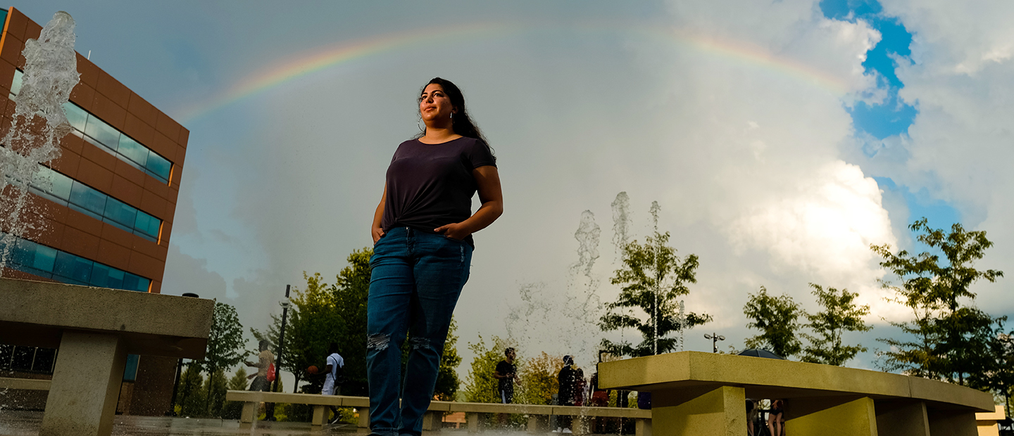 A young woman standing with her hands in her pockets on Oakland University's campus, with a rainbow and fountain behind her.