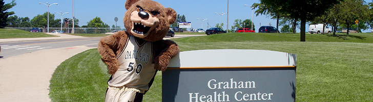 The Grizz bear mascot leaning on a sign outdoors that says Graham Health Center.