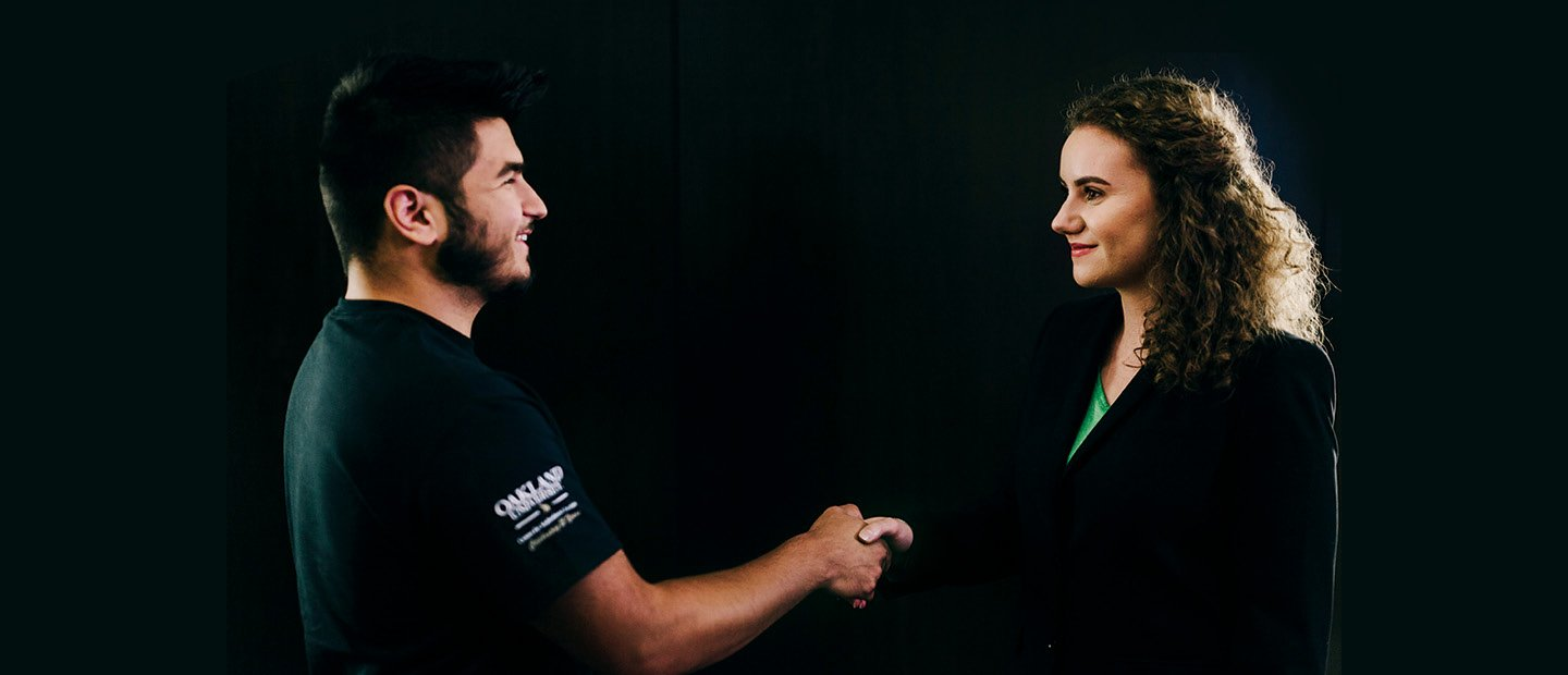 man and woman in black shaking hands against a black background