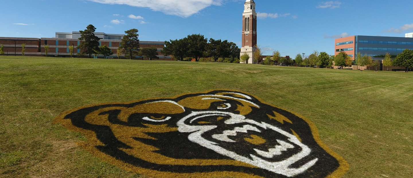 grizz head logo painted on the grass outside of the athletics building