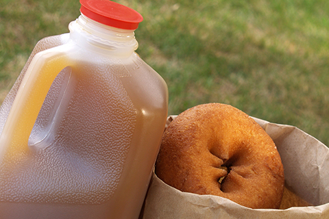 plastic jug of cider next to a paper bag filled with donuts