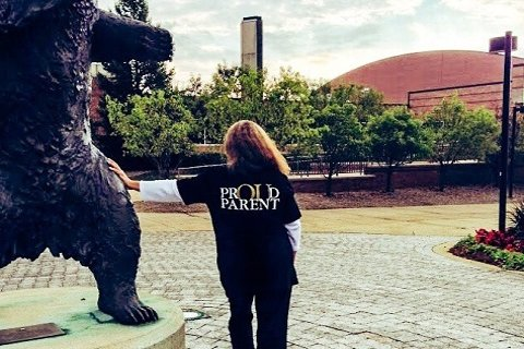 photo from behind of a person wearing a PrOUd Parent shirt, leaning on a statue of the Grizz mascot outside