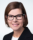 woman wearing glasses smiling at the camera