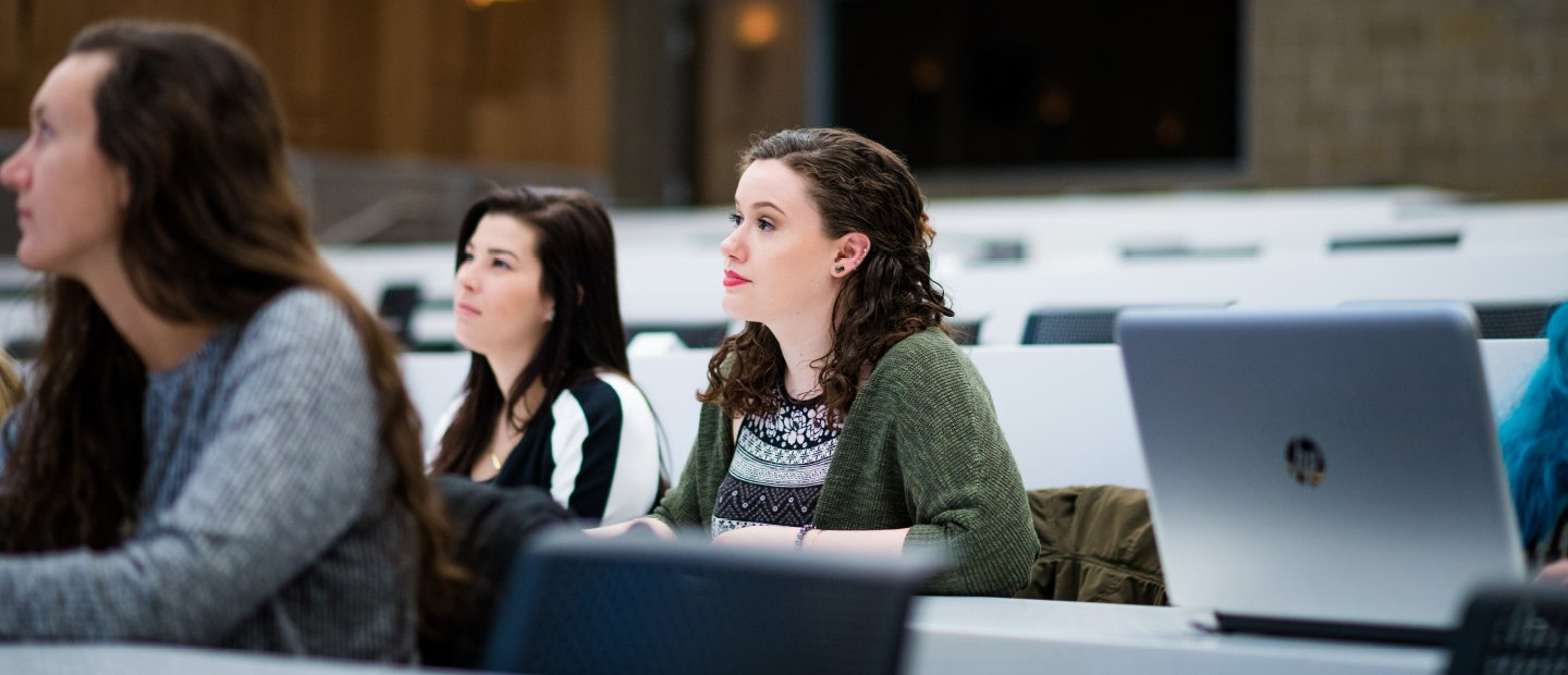 Three female students seated in a lecture hall