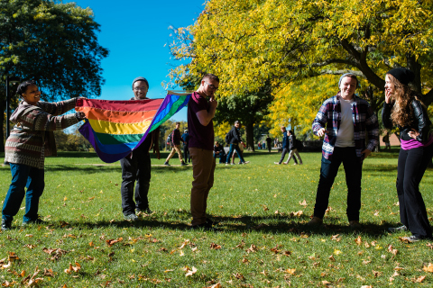 Students holding a rainbow flag while smiling