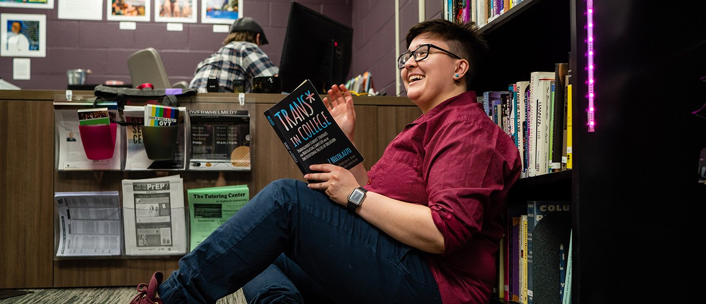 "young adult seated in front of a book shelf reading a book called ""Trans in College"""