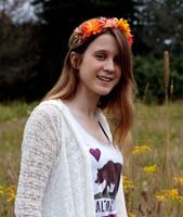 Sabrina Durso standing in a field with flowers in her hair
