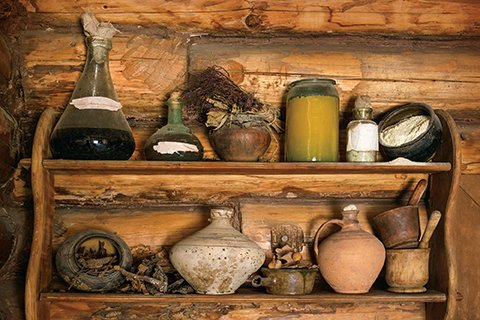 Containers of various size and shape lining two wooden shelves