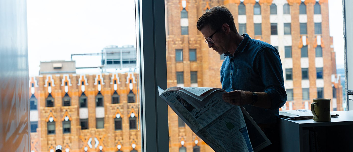 man reading a newspaper, standing in front of a window