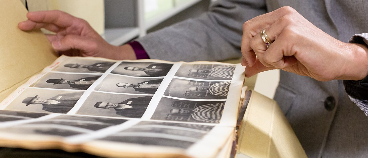 person flipping through a folder of old black and white photos of people