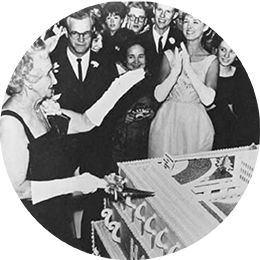 A black and white photo of a woman cutting a large cake at a formal celebration.