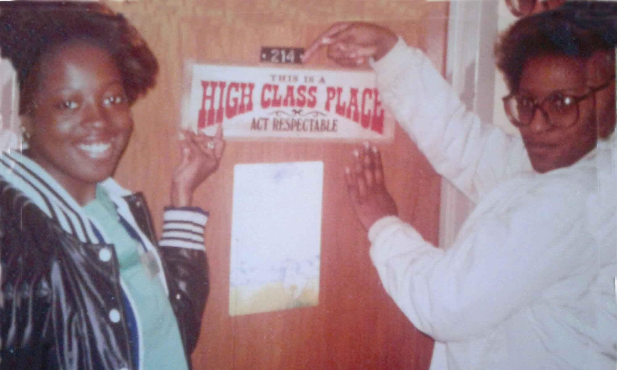 two women pointing to a sign on a door that says High Class Place