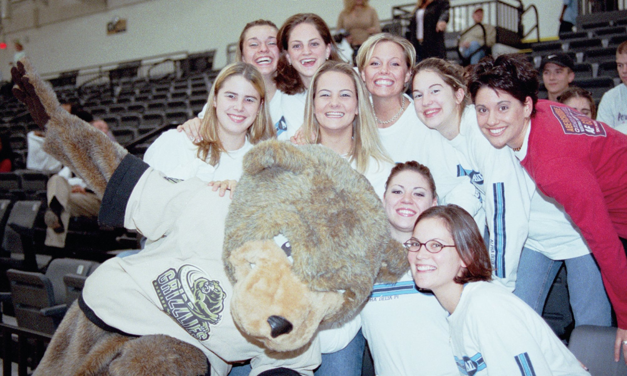 crowd of students surrounding the Grizz mascot at a sporting event