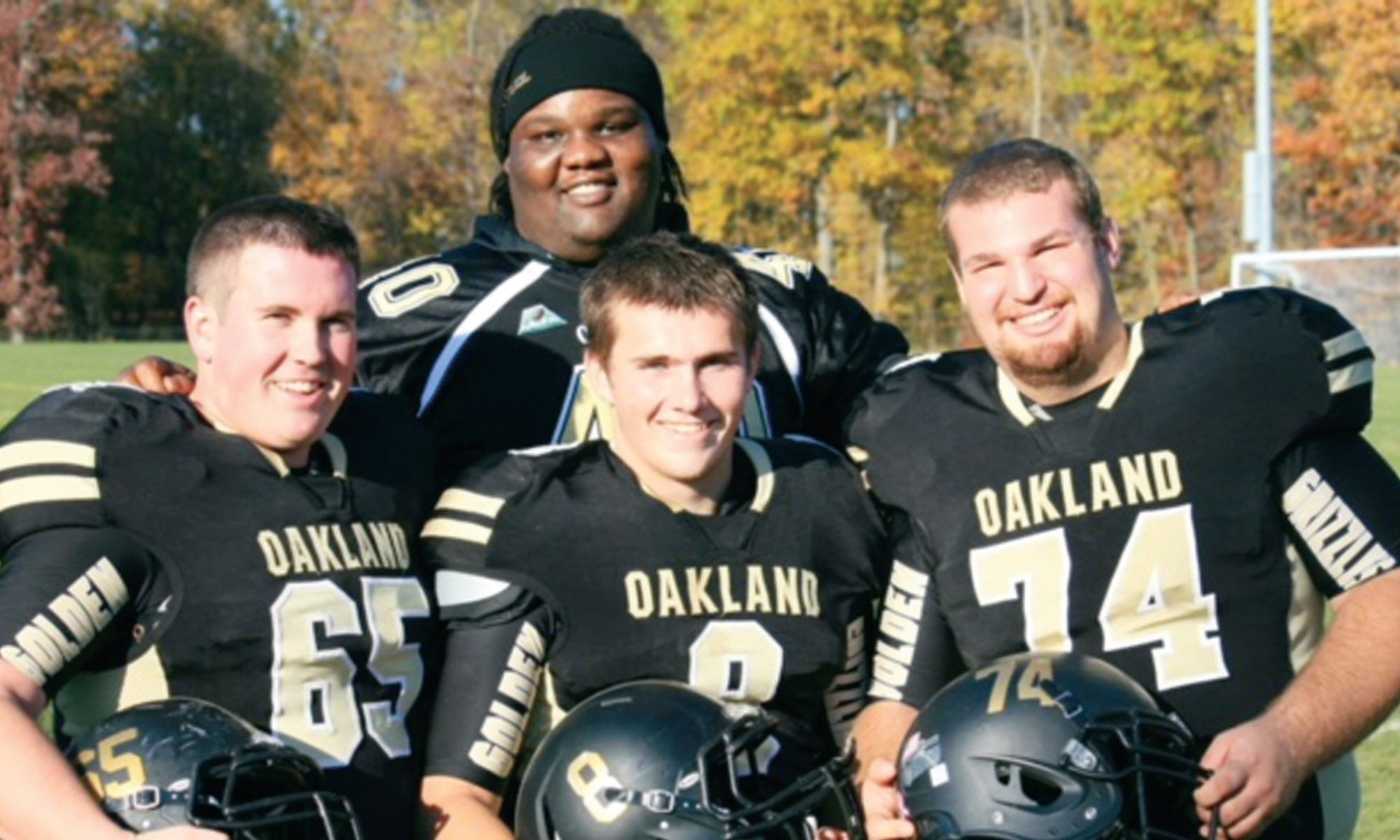 four men in Oakland University football uniforms, holding helmets