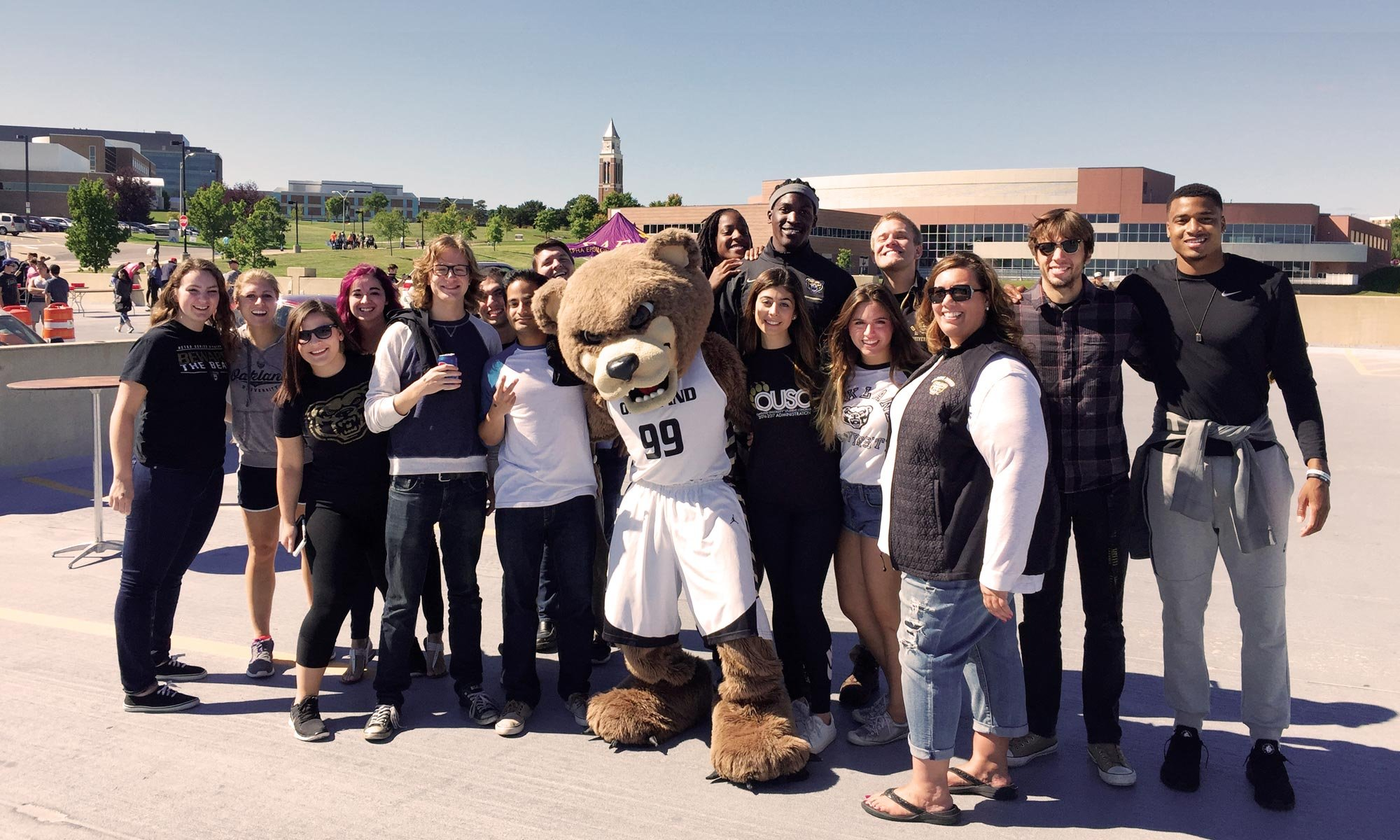 The Grizz posing for a photo with a group of students on a parking garage roof with a view of Elliott Tower in the background