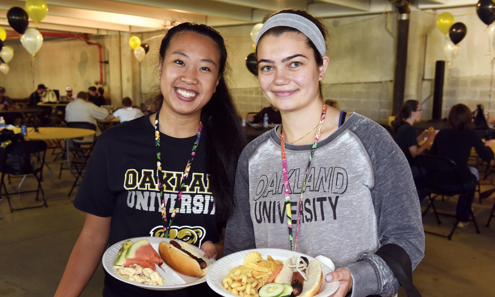 2 female students wearing Oakland University t-shits and posing for a photo while holding plates of food