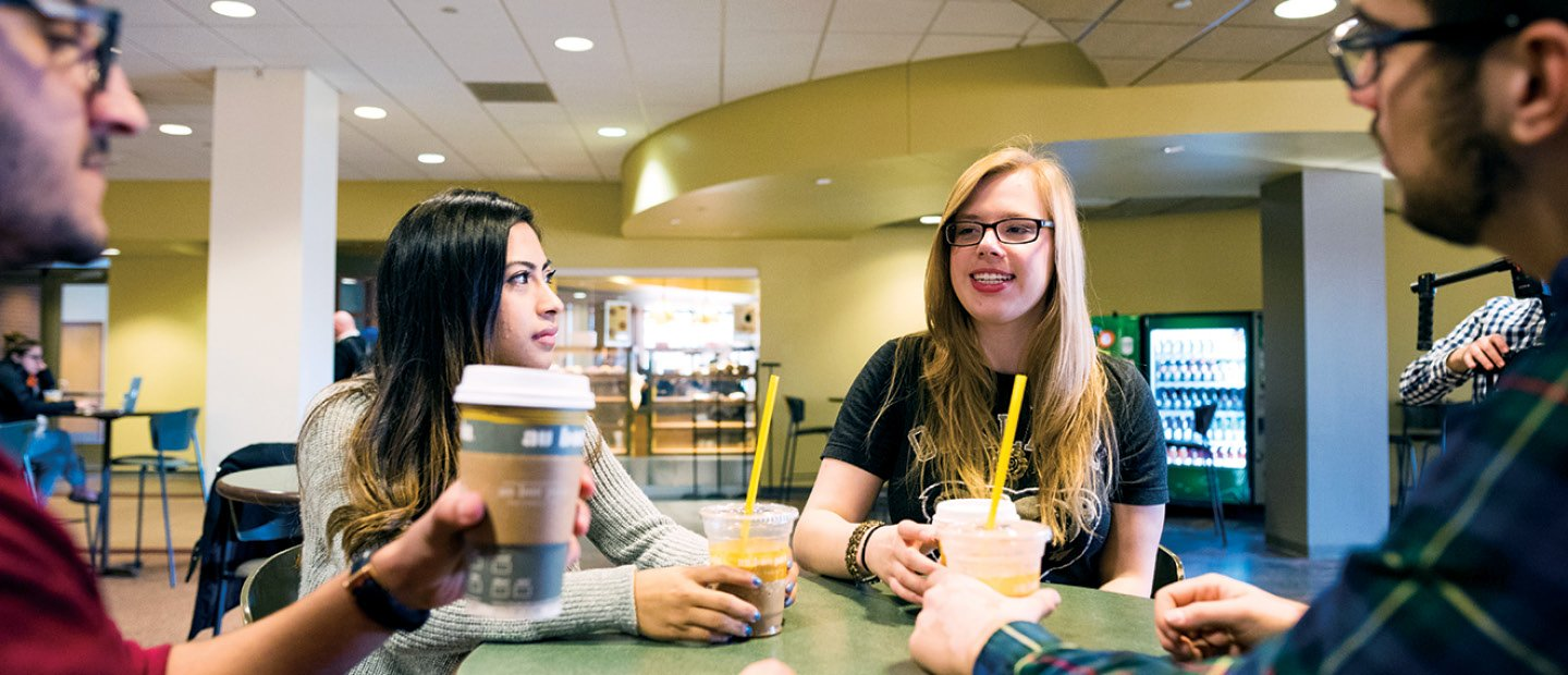 Students seated at a table with au bon pain cafe drinks