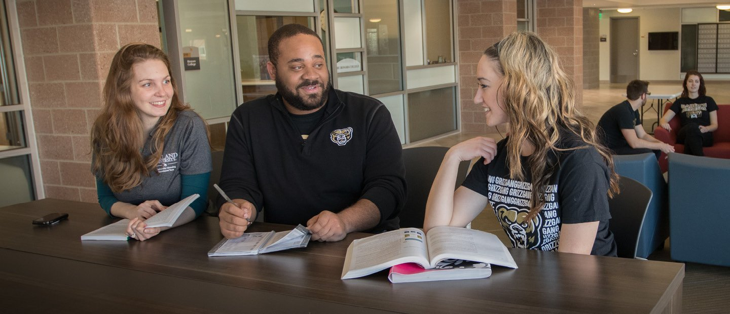 three people in Oakland University shirts seated at a table with open books