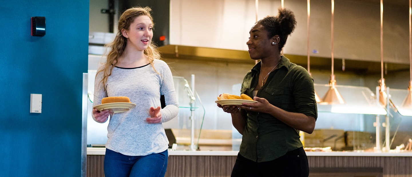 two female students carrying plates of food in a dining hall