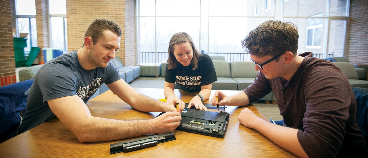 three students seated around a table, working with screwdrivers to examine a laptop