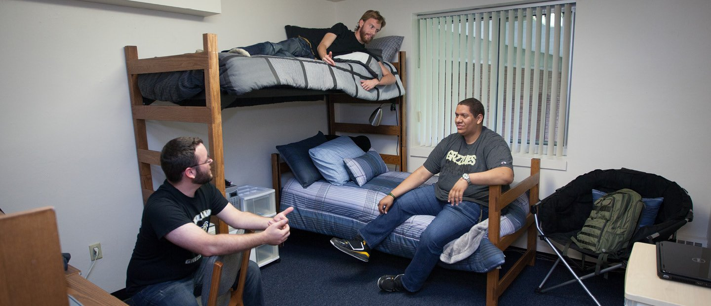 three men seated on furniture in a dorm room