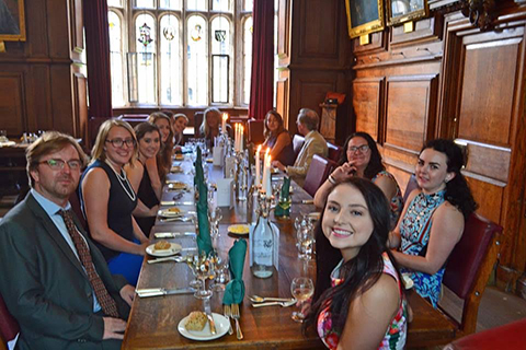 Group of O U study abroad students and professors seated at a long dining table in a wood-paneled room in Oxford, England