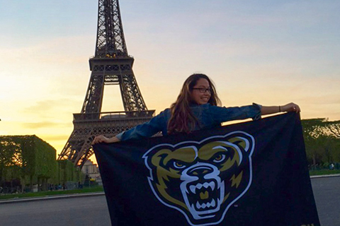 female student holding a flag with the Grizz head logo on it, Eiffel tower in the background