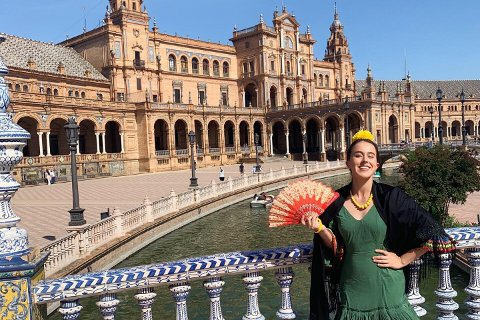 Woman standing on a bridge over water with an architectural building behind her in Seville, Spain.