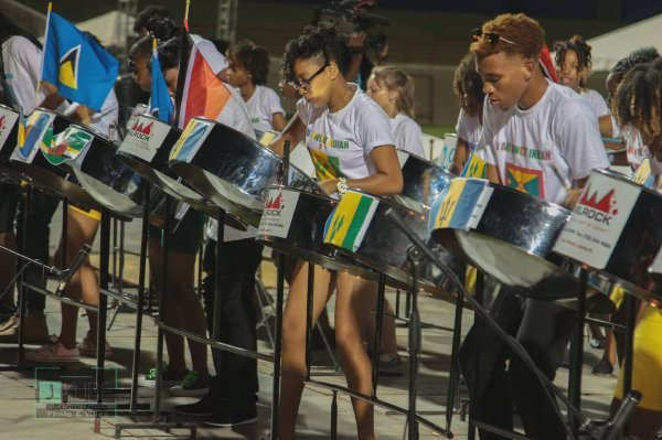 People playing steel drums with multi-colored flags on them