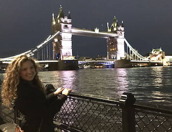 Brianna Tombaugh in front of a bridge over water in London at night