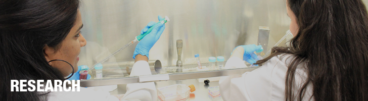 Research, two women wearing white coats and blue gloves in a lab holding test tubes