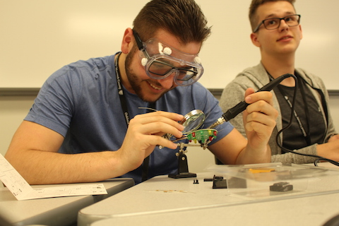 man wearing safety goggles working on an electrical device