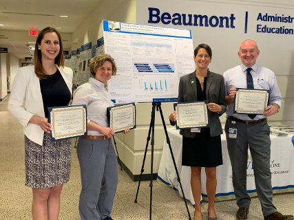 Four faculty members holding awards for poster presentation