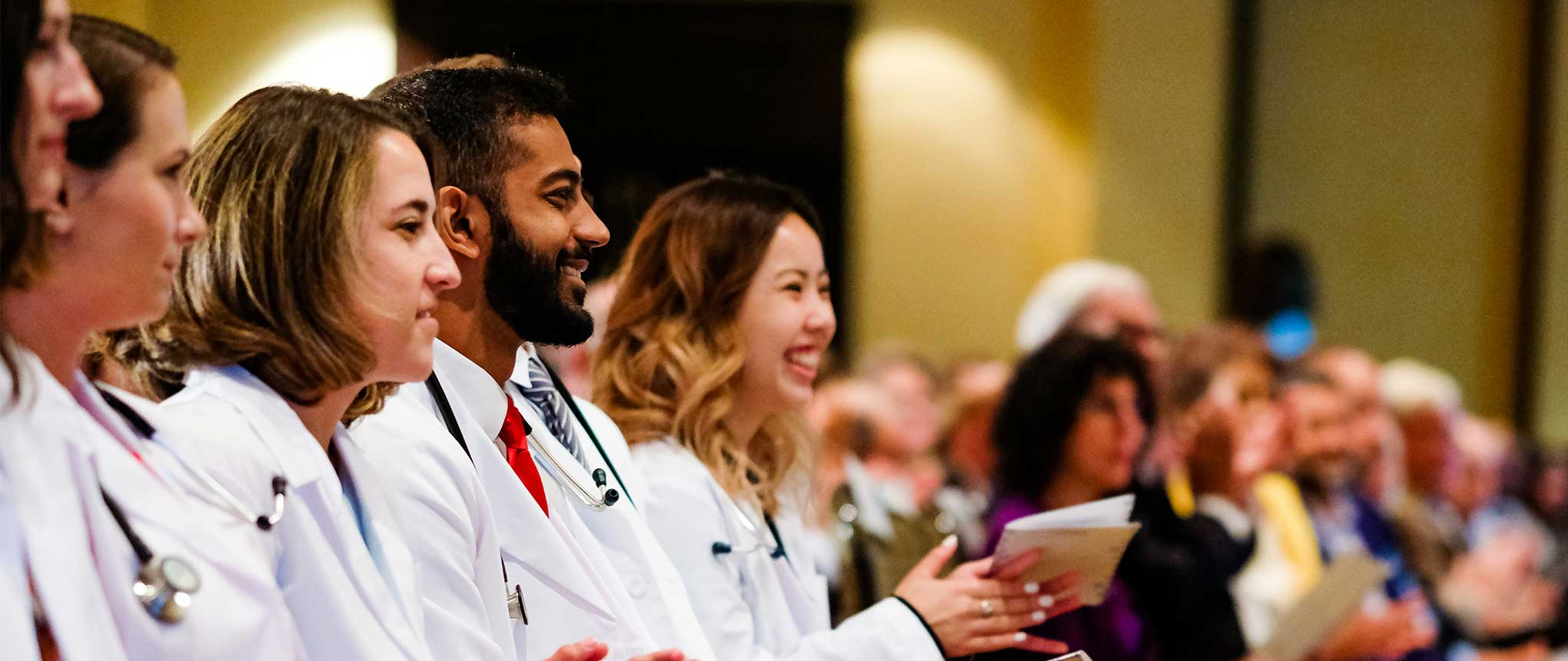 M1 students sit in their seats at the white coat ceremony. They are smiling and clapping toward the stage.