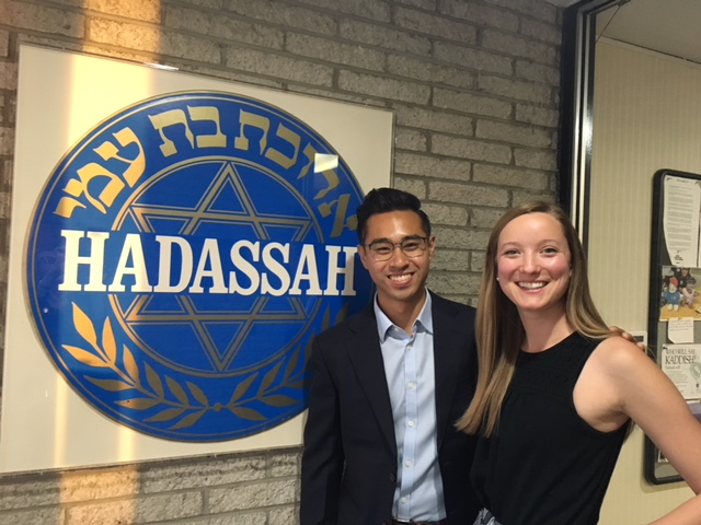 Two students who traveled to Hadassah stand, smiling, in front of a large plaque of the Hadassah Medical Center logo.