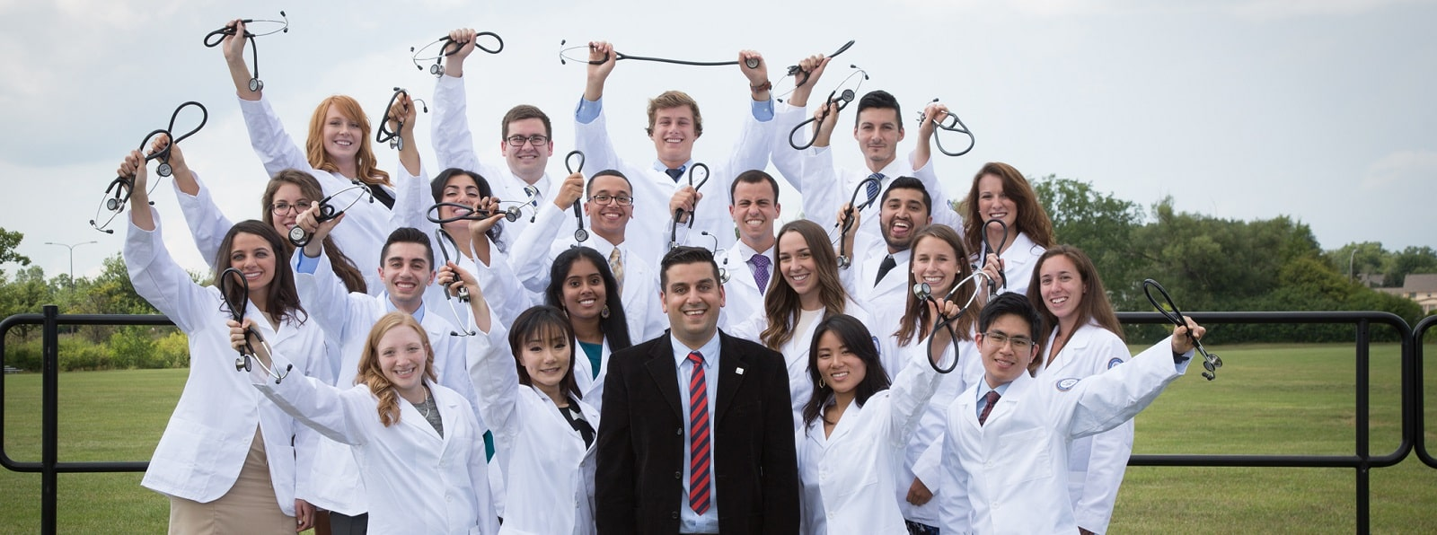 A PRISM group stands together wearing their white coats, smiling, and holding their stethoscopes above their heads.