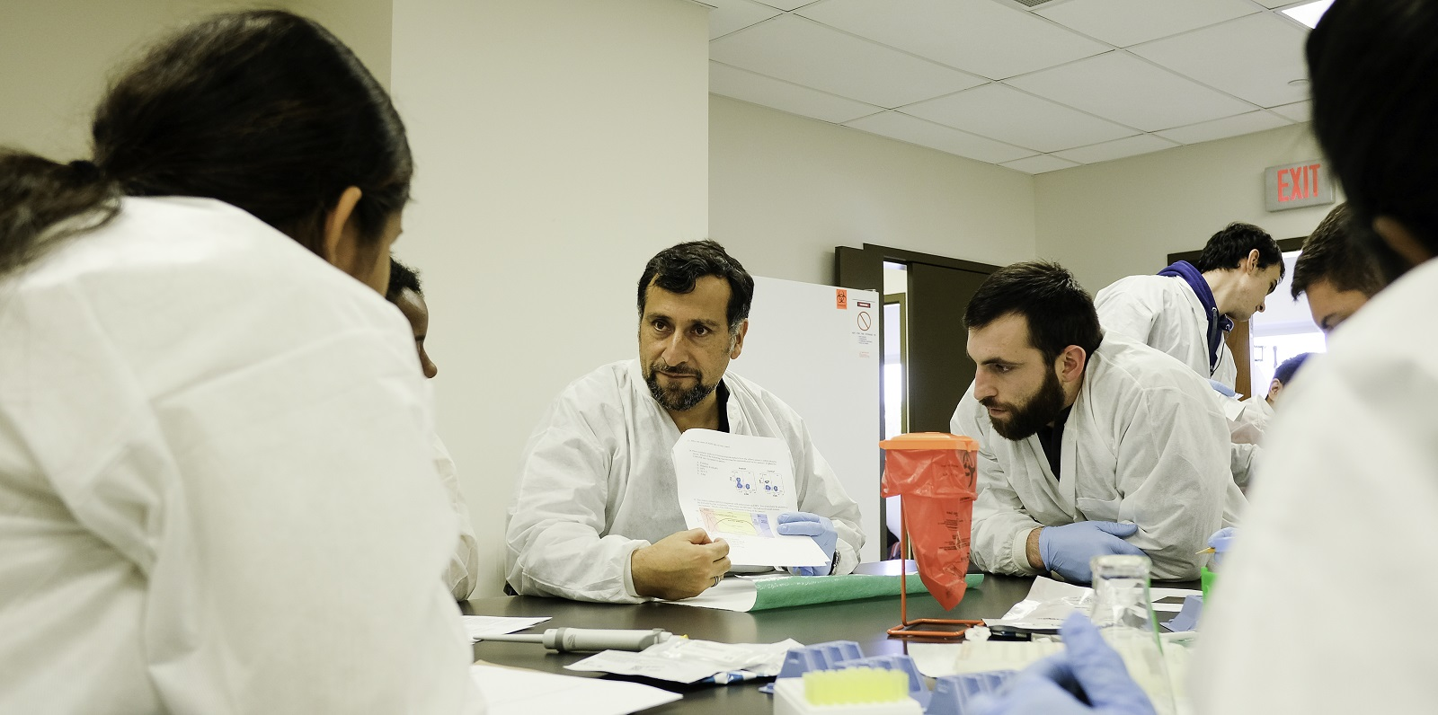 Dr. Claudio Cortes shows a graph on a piece of paper to a group of students who are huddled around a lab table