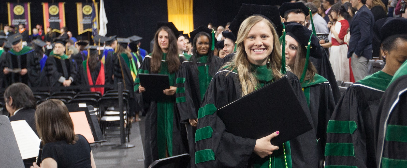 Student walks off stage at commencement holding her diploma holder, smiling at camera.