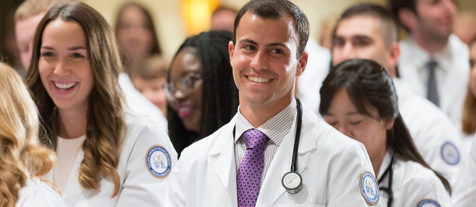 A student smiles as he stands in the crowd at the White Coat ceremony.