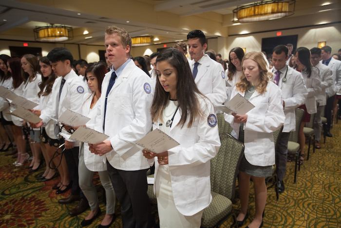 Students standing and reading programs at the White Coat Ceremony