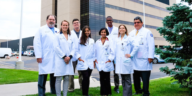 group of medical students and professionals in white lab coats posing for a photo outside