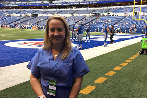 woman in blue scrubs standing on the sidelines at a football game