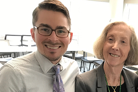 young man in a shirt and tie posing for a photo with an older female professor in a classroom