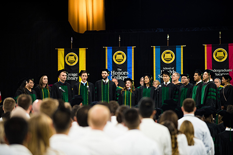 Class of 2018 members of O U W B's DocAppella choir singing on stage in front of colored flags at their commencement